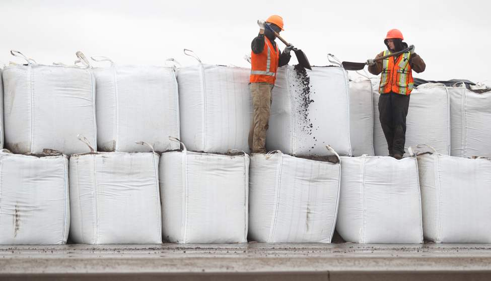 MIT workers work to fill super sandbags. Brandon Sun