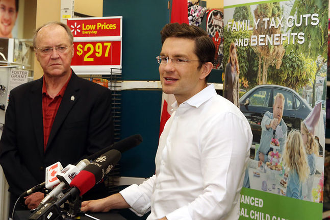 Employment Minister Pierre Poilievre, right, talks about the Universal Child Care Benefit as Conservative MP Keith Ashfield looks on during a press conference in Fredericton, N.B., on Thursday. While the Tories handed $3 billion to parents through the enhanced benefit, the money is taxable.