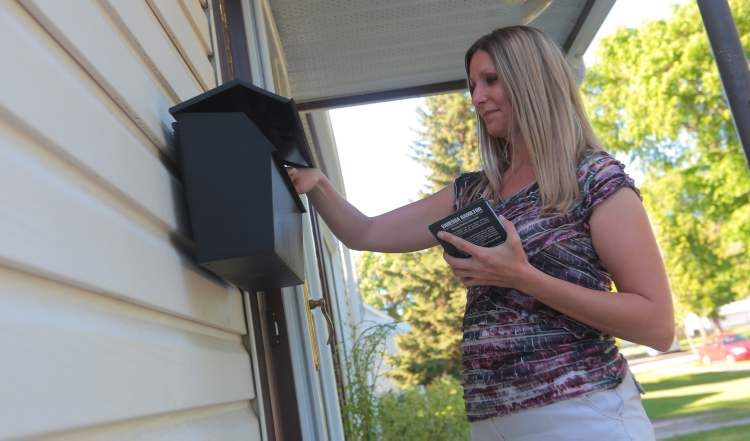 Brandon Sun Meadows Ward candidate Vanessa Hamilton puts a pamphlet in a mailbox while going door to door on Tuesday. (Bruce Bumstead/Brandon Sun)